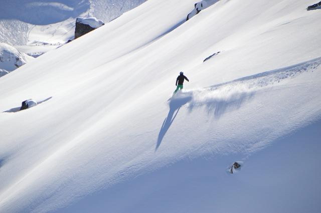 スノーボードで山の斜面を滑走